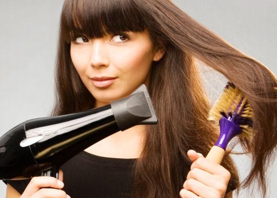 Mulher de cabelo comprido e castanho escuro segura escova com a mão esquerda e secador com a mão direita